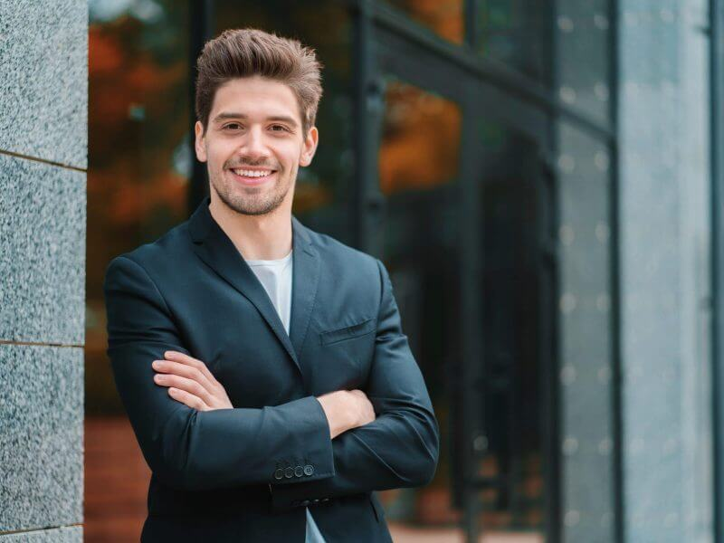 Portrait of young successful confident businessman in the city on office building background. Man in business suit looking to camera and smiling. Portraiture of handsome guy.